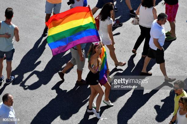 A participant holds a Rainbow Flag during the WorldPride 2017 parade in Madrid on July 1 2017 Revellers took to the rainbow streets of Madrid today...