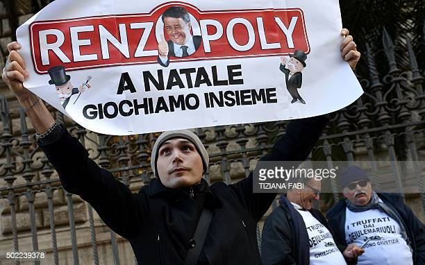 A participant holds a sign featuring an image of Italy's Prime Minister Matteo Renzi and reading 'Renzopoly at Christmas we play togheter' during a...