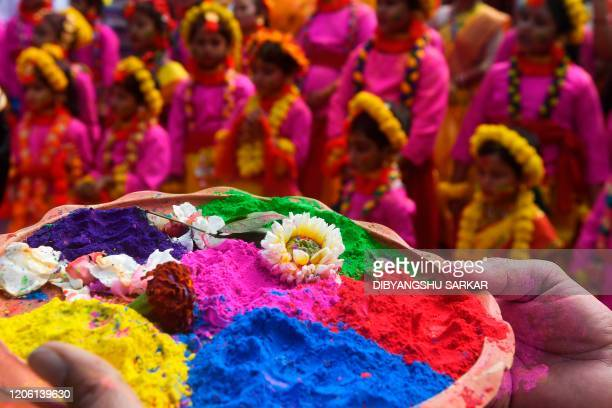 A participant holds a tray of coloured powder as students take part in a cultural procession to celebrate Holi the spring festival of colours in...