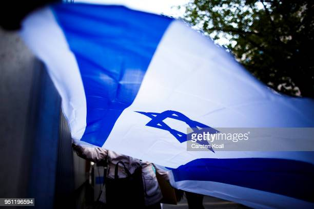 A participant holds an Israelian Flag during a wear a kippah gathering to protest against antiSemitism in front of the Jewish Community House on...