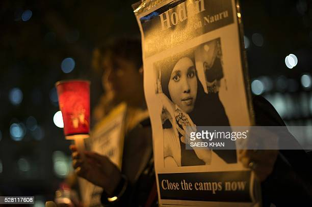 A participant holds portrait of a Somali refugee who set herself on fire on the remote Pacific island of Nauru during a candle light vigil in Sydney...