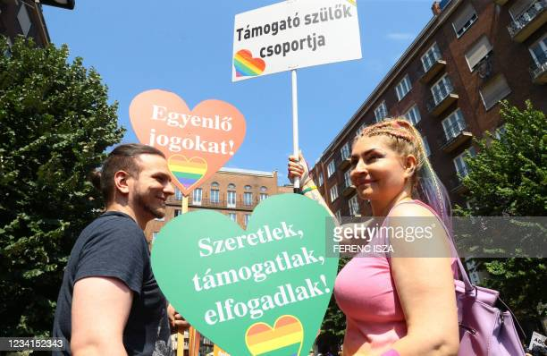 """Participant holds signs reading """"Group of supporting parents"""" and """"I love you, support you, accept you"""" during the lesbian, gay, bisexual and..."""