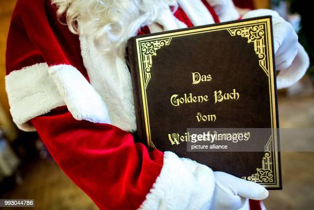 A participant holds up a book titled 'Das Goldene Buch vom Weihnachtsmann' during a Santa Claus training in Garssen a district of Celle Germany 4...