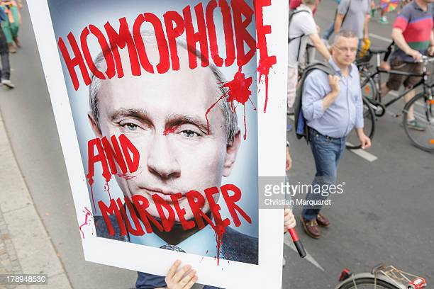 A participant holds up a picture from Wladimir Putin with the slogan 'Homophobe And Murderer' during a protest against homophobia in Russia on August...