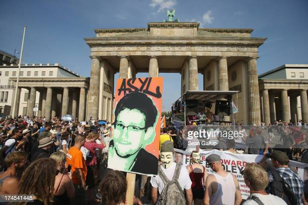 A participant holds up a picture of former NSA employee Edward Snowden with the word 'asylum' written above it at a protest gathering in front of the...