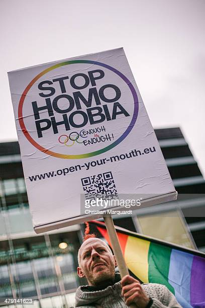 A participant holds up a picture with the slogan 'Stop Homophobia' during a protest against homophobia and racism in front of the Nordic Embassy on...