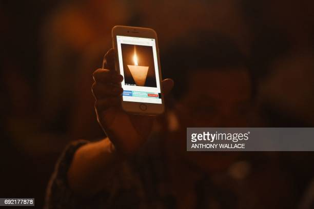 A participant holds up a smartphone showing an animated GIF image of a vigil candle as he and others attend a candlelight vigil at Hong Kong's...