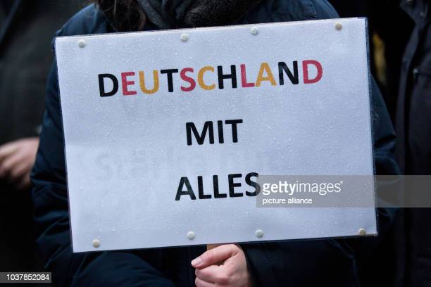A participant in a demonstration for cosmopolitanism holds up a sign that reads 'Germany with everything' in Kiel Germany 30 March 2015 Labour unions...