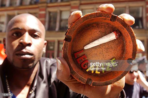 Participant in a pro-cannabis march holds up an ashtray with a fake marijuana cigarette in it May 4, 2002 in New York City. The marchers, who...