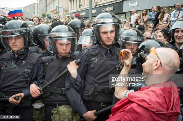 TOPSHOT A participant in an unauthorized opposition rally takes a picture of the riot police on Tverskaya street in central Moscow on June 12 2017...
