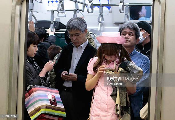 A participant in costume looks at her mobile phone as she rides on a train after Halloween celebrations at Shibuya district on October 31 2016 in...