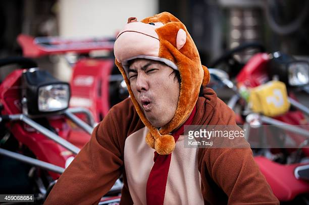 Participant in Donkey Kong costume poses for photo for the Real Mario Kart event in Tokyo on November 16 2014 in Tokyo Japan The organizer calls for...