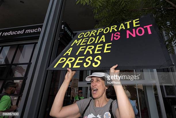 Participant in Enough is Enough protest holds a sign in front of the CNN building in Los Angeles California August 27 2016 People gathered to protest...