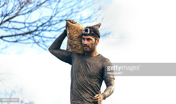 participant in extreme obstacle race carrying sandbags - sandbag stock pictures, royalty-free photos & images