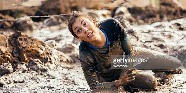 Participant in extreme obstacle race crawling under barbed wire