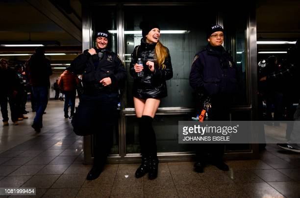 "Participant in the 18th Annual ""No Pants Subway Ride"" laughs with a police officers on January 13, 2019 in New York. - The ""No Pants Subway Ride"" is..."