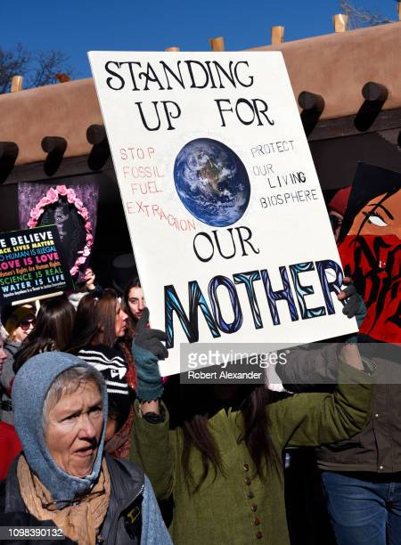 A participant in the 2019 Women's March holds a sign urging an end to fossil fuel extraction during a rally in Santa Fe New Mexico