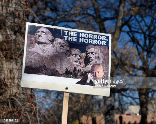 Participant in the 2019 Women's March in Santa Fe, New Mexico, holds up an anti-Trump sign reflecting her opposition to U.S. President Donald Trump...