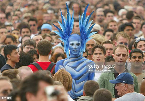 A participant in the annual Gay Pride Parade stands while dressed in a blue costume June 29 2002 in Paris France Up to a half million people marched...