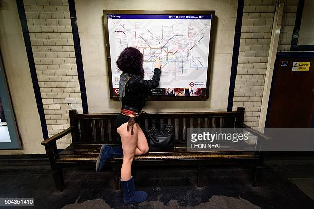 A participant in the annual International 'No Pants Subway Ride' poses as she looks at a London underground tube map at a station in London on...
