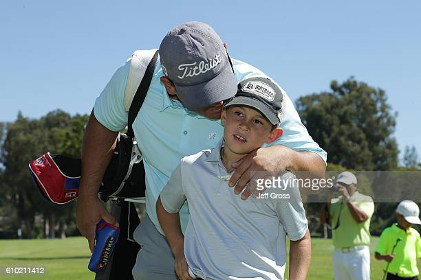A participant in the boys 79 division receives some advice from his father prior to the putting competition during a regional round of the Drive Chip...