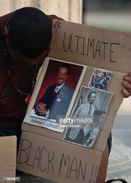 A participant in the candlelight vigil for bows his head as he holds a cardboard with images of the late attorney Johnnie L Cochran at a candlelight...
