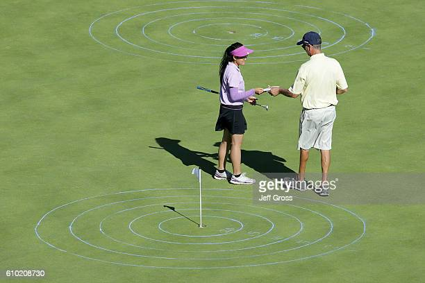 A participant in the girls 1415 age group gives her scorecard to an official in the putting competition during a regional round of the Drive Chip and...
