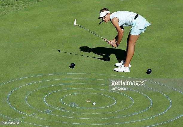 A participant in the girls 1415 age group reacts to a putt in the putting competition during a regional round of the Drive Chip and Putt Championship...