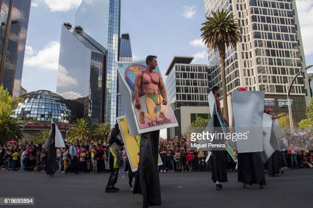 A participant in the parade during the Day of the Dead Celebrations in Mexico City shows a giant card featuring'The World' while walking across...