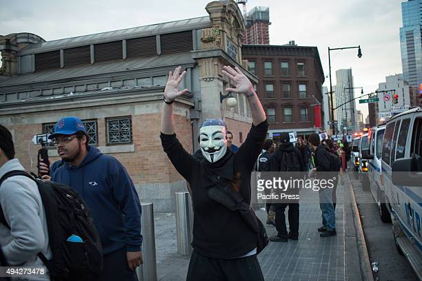 A participant in the rally wearing a Guy Fawkes mask raises her hands and chants 'Hands Up Don't Shoot' while marching along Flatbush Avenue...