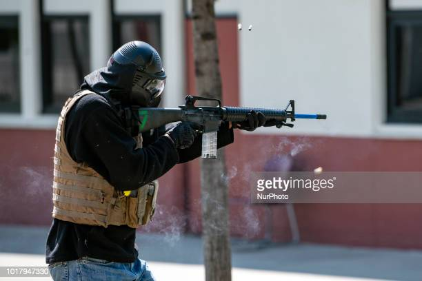 A participant in the role of a school shooter fires a gun during an active shooter drill in a high school near Los Angeles California on August 16...
