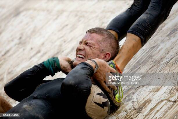 A participant in the Tough Mudder obstacle course braces himself as he helps a fellow competitor climb up the human pyramid during the 103 mile trail...