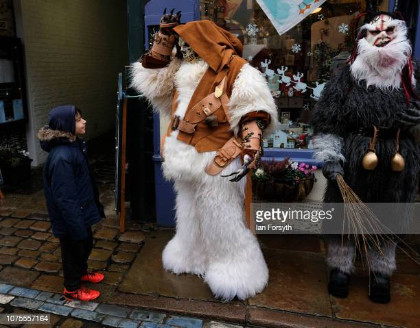 A participant interacts with a child as they parade through the streets during the annual Whitby Krampus parade on December 01 2018 in Whitby England...