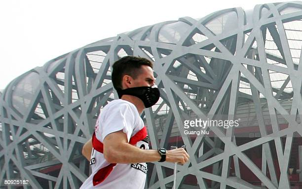 Participant is shrouded with smog as he takes part in a long-distance race outside the National Stadium, also known as the 'Bird's Nest' on April 30,...