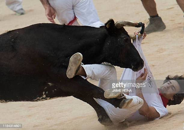 TOPSHOT A participant is tossed by a heifer during the first bullrun of the San Fermin festival in Pamplona northern Spain on July 7 2019 On each day...