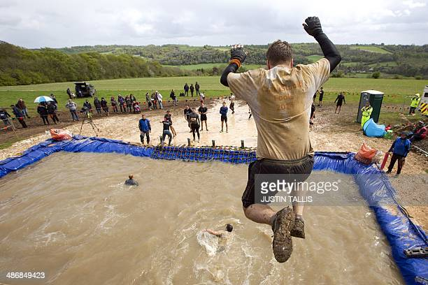 Participant jump from a four meter high platform into water during the Tough Mudder endurance race in Henley on Thames West of London on April 26...