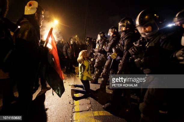 A participant knees in front of the riot police line outside the headquarter of the Hungarian state television as demonstrators of a rally by members...