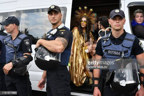 Participant looks around while sitting in a bus as policemen stand guard during the annual Gay Pride parade in Kiev on June 23, 2019. - More than...
