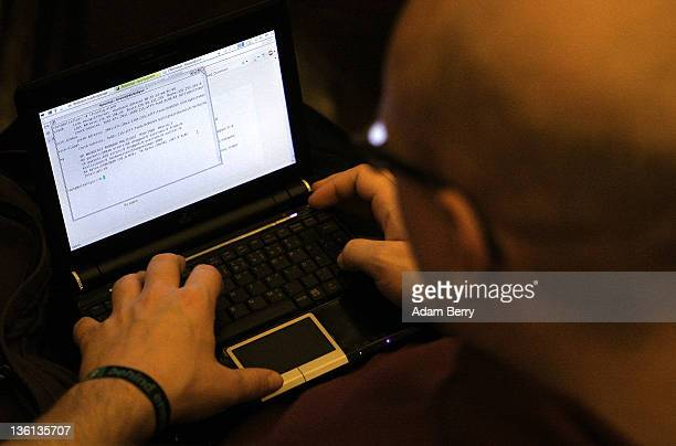 A participant looks at lines of code on a laptop on the first day of the 28th Chaos Communication Congress Behind Enemy Lines computer hacker...