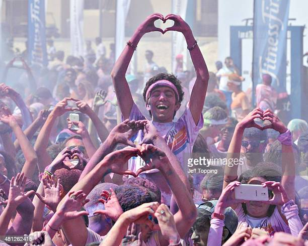 A participant makes the shape of a heart with others as they celebrate listening to music after finishing The Color Run presented by Active life...