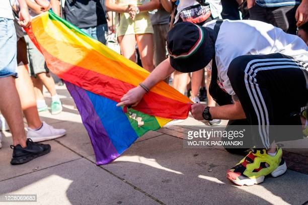 Participant of a demonstration against the 'LGBT' rights movement burns a rainbow flag in front of the Warsaw University, on August 16, 2020.