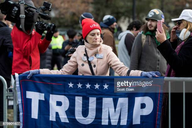 A participant of an AltRight organized free speech event drapes a Trump campaign flag at the Boston Common on November 18 2017 in Boston...