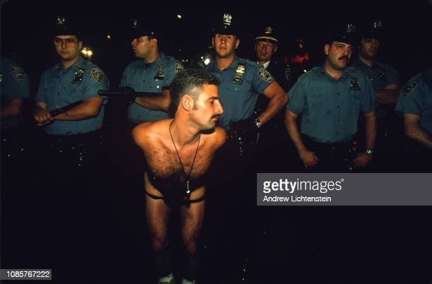 A participant of the annual gay pride celebrations shows off his skimpy clothing to members of the New York City police department in June of 1993 in...