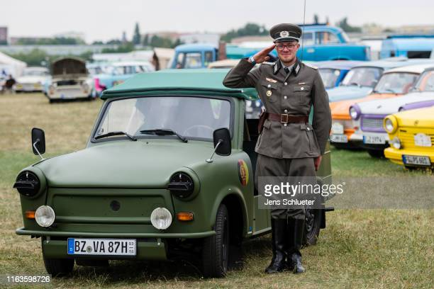 A participant of the annual meeting of the Trabant fans poses next to a Trabant for a photo on August 24 2019 in Zwickau Germany The humble Trabant...