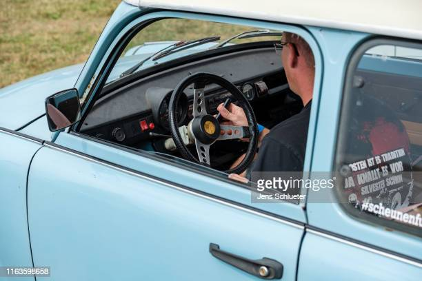 A participant of the annual meeting of the Trabant fans sits in a Trabant on August 24 2019 in Zwickau Germany The humble Trabant or Trabi as many...