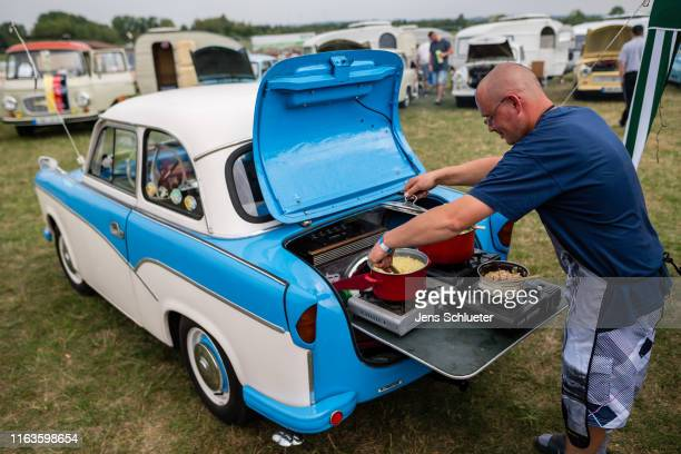 A participant of the annual meeting of the Trabant fans sits in front of a converted Trabant and cooks a lunch on 24 August 2019 in Zwickau Germany...