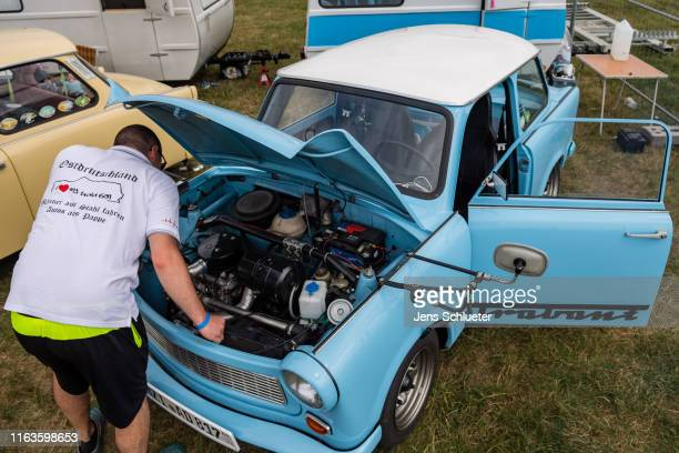 A participant of the annual meeting of the Trabant fans stands in the front of a Trabant on August 24 2019 in Zwickau Germany The humble Trabant or...