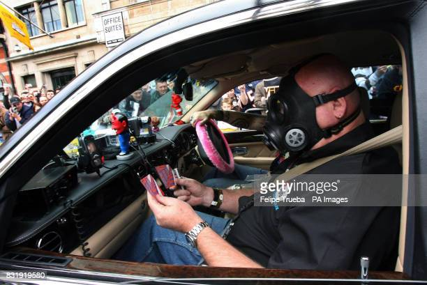 A participant of the car rally Gumball 3000 checks their new 'passports' given at the start of the race at Pall Mall in London