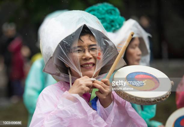 A participant of the formation 'Love Korea Koreanischer Verein' protects herself from rain during the 22nd Carnival of Cultures in Berlin Germany 4...