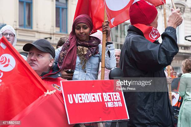 """Participant of the mayday march in Ghent is seen with in the foreground the slogan """"You deserve better""""."""